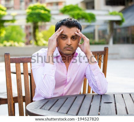 Closeup portrait, stressed young businessman, sitting at table, hands on head with bad headache, isolated background of trees, buildings, outside. Negative human emotion facial expression feelings. - stock photo