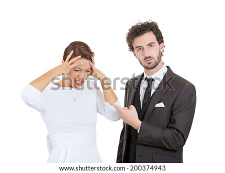 Closeup portrait stressed young couple going through relationship hard times isolated white background. Upset angry husband blaming his wife for wrong doing something woman has headache from screaming