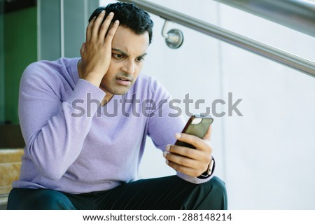Closeup portrait, stressed young man in purple sweater, shocked surprised, horrified disturbed, by what he sees on his cell phone, isolated indoors background. - stock photo