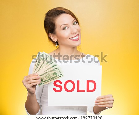 Closeup portrait, super happy excited successful young business woman holding money dollar bills in hand and red sold sign, isolated yellow background. Positive emotion feeling. Financial reward - stock photo