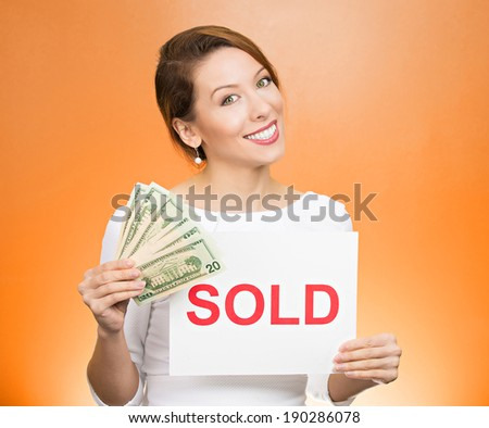 Closeup portrait, super happy excited successful young business woman holding money dollar bills in hand and red sold sign, isolated orange background. Positive emotion feeling. Financial reward - stock photo