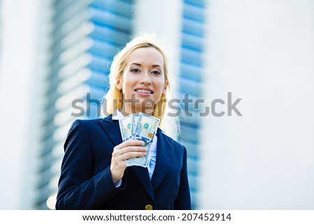 Closeup portrait super happy excited successful young business woman holding money dollar bills in hand isolated corporate office background. Positive emotion face expression feeling. Financial reward - stock photo