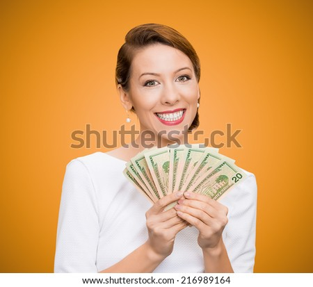 Closeup portrait super happy excited successful young business woman holding money dollar bills in hand, isolated orange background. Positive emotion facial expression feeling. Financial reward - stock photo