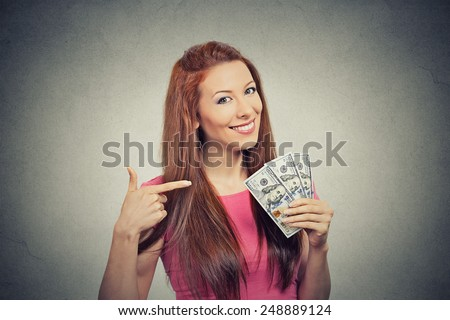 Closeup portrait super happy excited successful young business woman holding money dollar bills in hand isolated grey wall background. Positive emotion facial expression feeling. Financial reward - stock photo