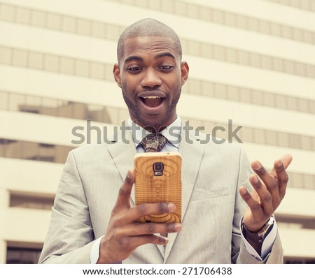 Closeup portrait surprised handsome young man looking at phone seeing unexpected news photos email isolated outside city building background. Human emotion, reaction, facial expression - stock photo