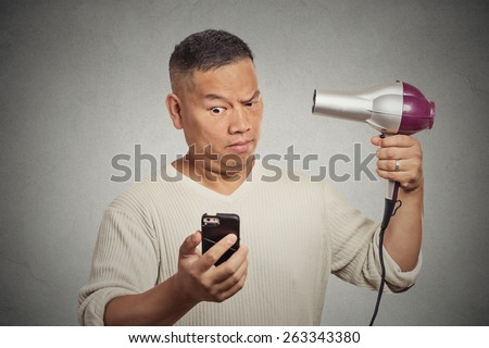 Closeup portrait surprised skeptical man reading social media news on smartphone looking at mobile phone holding hairdryer isolated on grey wall background. Human face expression. Mind blowing deal  - stock photo