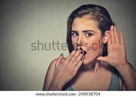 Closeup portrait surprised young nosy woman hand to ear gesture carefully intently secretly listening juicy gossip conversation news privacy violation isolated grey background. Human face expression - stock photo
