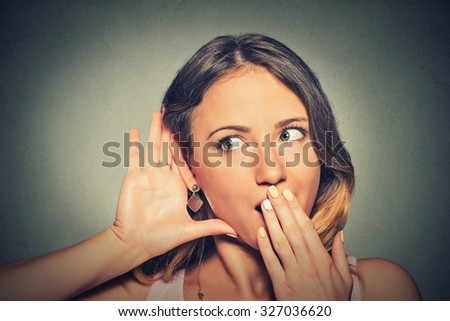 Closeup portrait surprised young nosy woman hand to ear gesture carefully intently secretly listening juicy gossip conversation news isolated grey background. Human face expression. Privacy violation - stock photo