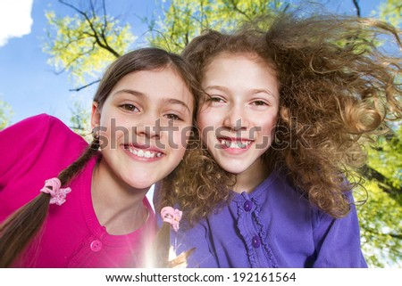 Closeup portrait sweet little two sisters happy smiling, relaxed excited girls playing outdoors, sunshine, vacation summer time isolated trees background. Childhood, positive emotion facial expression - stock photo