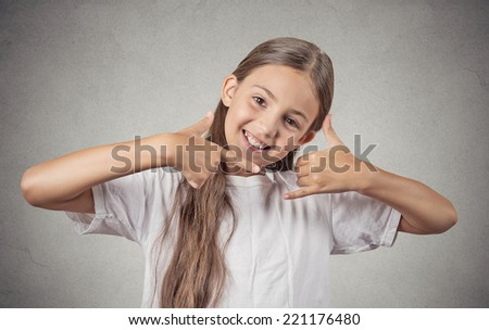 Closeup portrait  teenager girl making call me gesture sign with hand shaped like phone, isolated grey wall background. Positive human emotions, face expressions, body language, communication - stock photo