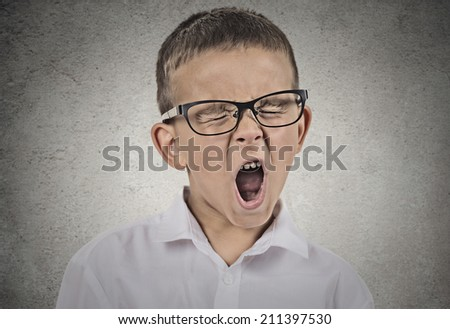 Closeup portrait tired child with glasses yawning, isolated on grey wall background. Human facial expressions, emotions, feelings, body language. Long school hours, busy day concept.  - stock photo