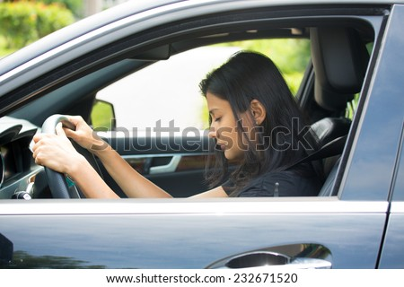 Closeup portrait tired young attractive woman with short attention span, driving her car after long hours trip, trying to stay awake at wheel, isolated outside background. Sleep deprivation - stock photo