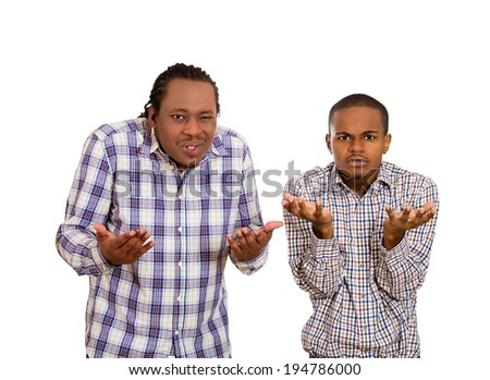 Closeup portrait two angry, unhappy young men, managers arms out asking what's problem who cares so what, I don't know. Isolated white background. Negative human emotions, facial expressions, feelings - stock photo