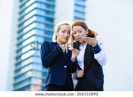 Closeup portrait two upset sad unhappy, surprised, shocked women looking at smart phone, reading text, e-mail isolated office background. Negative human emotions, facial expression, reaction. Bad news - stock photo