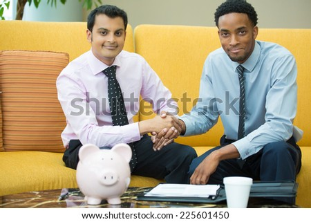 Closeup portrait, two young men in ties shaking hands, isolated yellow couch background with piggy bank and coffee on table foreground - stock photo