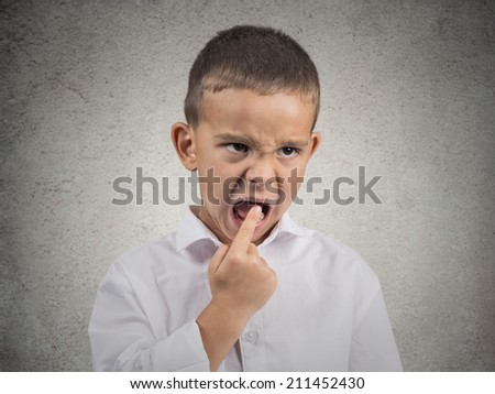 Closeup portrait unhappy angry, annoyed pissed off boy with finger in mouth looking with funny negative facial expression, disapproval, isolated grey wall background. Human emotion sign, body language - stock photo