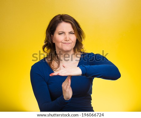 Closeup portrait, unhappy attractive young serious woman showing time out gesture with hands isolated yellow background. Negative human emotion facial expression, sign symbol, body language, attitude - stock photo