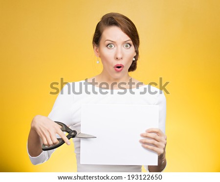Closeup portrait unhappy, confused, surprised, shocked business woman, funny looking female, worker employee cutting blank white paper, copy space, scissors isolated yellow background. Face expression - stock photo