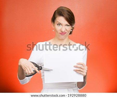 Closeup portrait, unhappy, skeptical, confused, displeased business woman, funny female, worker, employee cutting blank white paper, copy space, scissors isolated red background. Facial expressions - stock photo