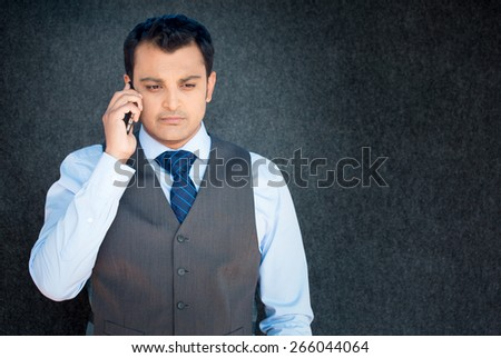 Closeup portrait, unhappy worried young man in vest and tie talking on phone, isolated gray black background. Negative human emotions, facial expressions, feelings, reaction. Bad news. - stock photo