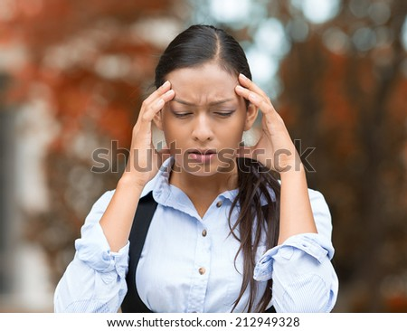 Closeup portrait unhappy young business woman hands on head stressed bothered by mistake having bad headache migraine isolated outdoor park background. Negative human emotion facial expression feeling - stock photo