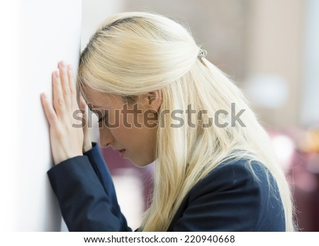 Closeup portrait unhappy young business woman, head on wall, bothered by mistake having bad headache isolated background corporate office. Negative human emotion, facial expression feeling reaction - stock photo