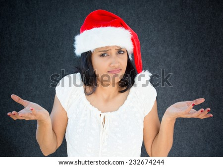 Closeup portrait, unhappy, young, pretty  woman in red santa claus hat, asking why, whats the problem, who cares, so what, I dont know. Isolated gray black background. Negative human emotions - stock photo