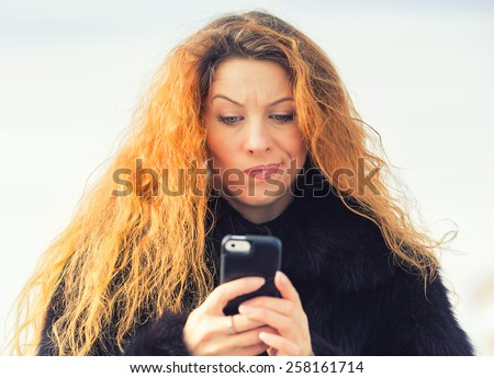 Closeup portrait upset sad skeptical unhappy serious woman talking texting on mobile phone displeased with conversation isolated outdoor background. Negative human emotion face expression feeling - stock photo