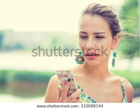 Closeup portrait upset sad skeptical unhappy serious woman talking texting on phone displeased with conversation isolated park outdoors background. Negative human emotion face expression feeling - stock photo