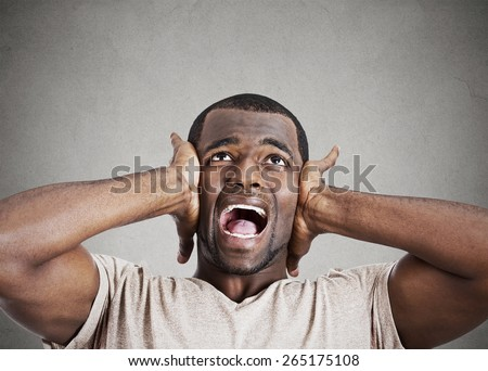 Closeup portrait upset stressed young man squeezing his head, going nuts, screaming, losing his mind, looking up isolated gray wall background. Negative emotion feeling reaction  - stock photo