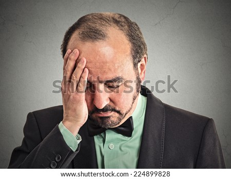 Closeup portrait very sad, depressed, alone, disappointed upset man resting his face on hand looking down isolated on grey wall background. Human mood expression, emotions, feeling, life perception - stock photo