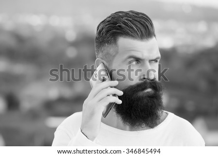 Closeup portrait view of one handsome young pensive man with long dark haired beard speaking on mobile phone outdoor on blurred natural background black and white, horizontal picture - stock photo