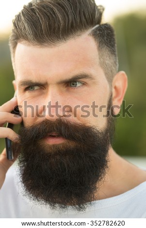 Closeup portrait view of one handsome young pensive man with long dark haired beard speaking on mobile phone outdoor on blurred green natural background, vertical picture - stock photo