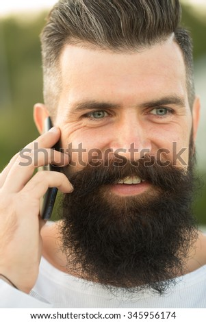 Closeup portrait view of one handsome young smiling man with long dark haired beard speaking on mobile phone outdoor on blurred green natural background, Vertical picture - stock photo