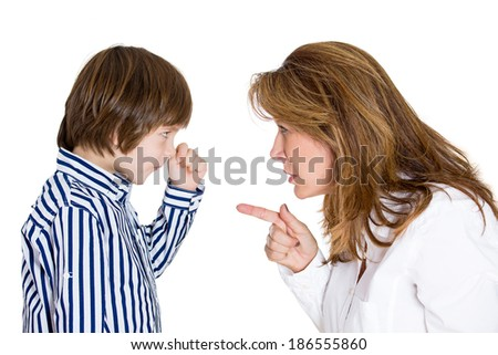 Closeup portrait, woman pointing finger at boy because he did something wrong go to room. Kid is defiant, fist up. Isolated white background. Negative human emotion facial expression conflict - stock photo