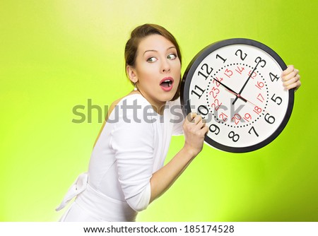 Closeup portrait woman, worker, holding clock looking anxiously, pressured by lack, running out of time, isolated green background. Human face expression, emotion, reaction, corporate life style - stock photo