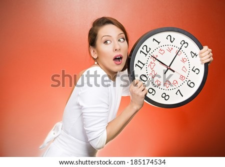 Closeup portrait woman, worker, holding clock looking anxiously, pressured by lack, running out of time, isolated red background. Human face expression, emotion, reaction, corporate life style - stock photo