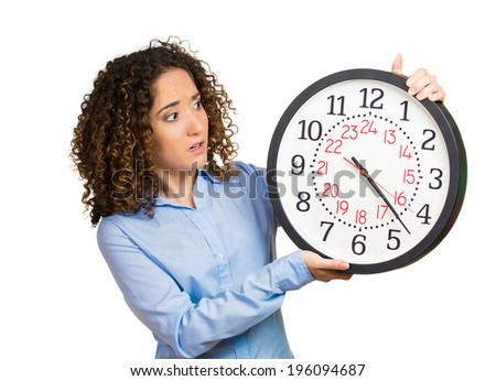 Closeup portrait woman, worker, holding clock looking anxiously, pressured by lack, running out of time isolated white background. Human face expression, emotion, reaction, corporate life. Last moment