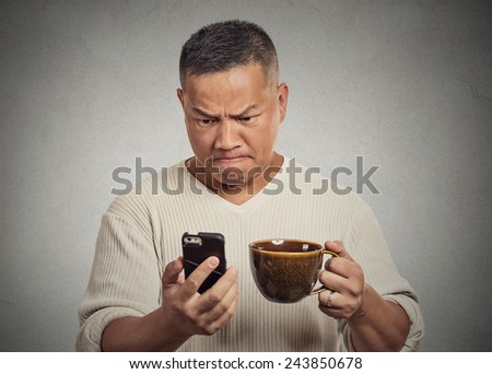 Closeup portrait worried angry frustrated man reading bad news sms on smart mobile phone drinking holding cup coffee tea isolated grey wall background. Human face expression emotion reaction - stock photo