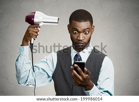 Closeup portrait worried, shocked business man, deal maker reading bad news on smart, mobile phone holding hairdryer isolated black grey background. Human face expression, emotion, corporate executive - stock photo