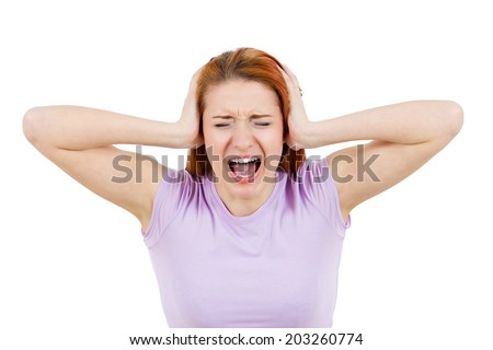 Closeup portrait worried, stressed, overwhelmed young woman, funny looking girl, covering her ears, screaming going crazy, isolated white background. Human emotions, facial expression, life perception - stock photo