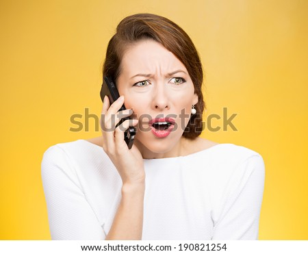 Closeup portrait young angry business woman, corporate employee talking on cell phone, having unpleasant, bad conversation, isolated yellow background. Negative emotions, facial expressions, reaction - stock photo