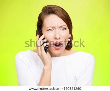 Closeup portrait young angry business woman, corporate employee talking on cell phone, having unpleasant, bad conversation, isolated green background. Negative emotions, facial expressions, reaction - stock photo