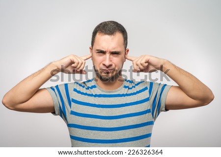 Closeup portrait young, angry, unhappy, stressed man covering his ears - stock photo