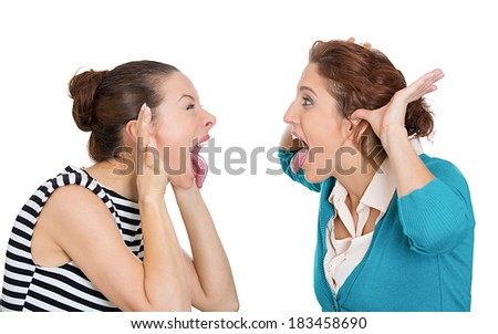 Closeup portrait young angry women, screaming, tongues out at each other, blaming for problem, mistakes, isolated white background. Friendship difficulties concept negative emotion expression feeling - stock photo