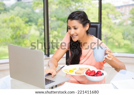 Closeup portrait, young, attractive businesswoman, kick start day with healthy breakfast, smiling on laptop. Isolated glass window indoor green trees background. The early bird catches the worm. - stock photo