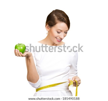 Closeup portrait young attractive happy, fit woman, girl in white dress, holding green apple, measuring her waist isolated white background, clipping path. Healthy life style, nutrition. Positive. - stock photo
