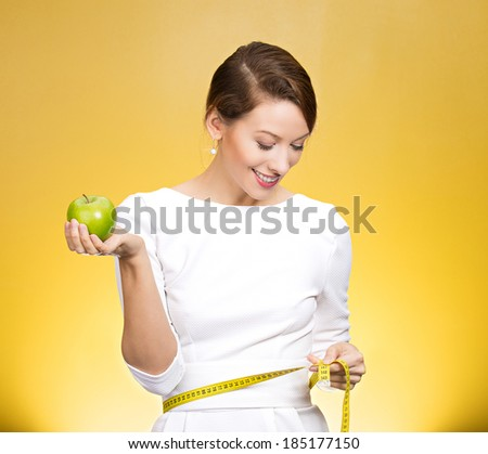 Closeup portrait young attractive, happy,  fit woman in white dress, holding green apple, measuring her waist, isolated yellow background. Healthy life style, nutrition. Positive emotion, expression - stock photo