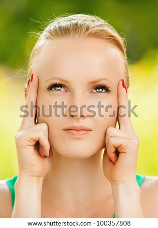 Closeup portrait young beautiful woman touching temples at summer green park - stock photo
