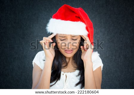 Closeup portrait, young beautiful worried stressed wife, mother, woman in santa claus hat with hands on temples looking down, isolated gray black background. Last minute christmas shopping - stock photo